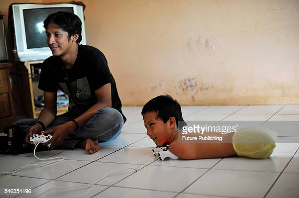 Tyo Satrio a little boy born without arms and legs seen playing video game at his house in Panawangan Ciamis on February 13 2016 in West Java...