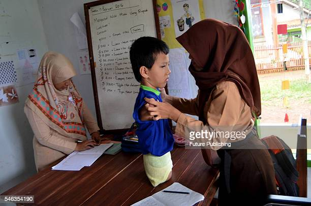 Tyo Satrio a little boy born without arms and legs seen with his teachers at school in Panawangan Ciamis on February 13 2016 in West Java Indonesia...