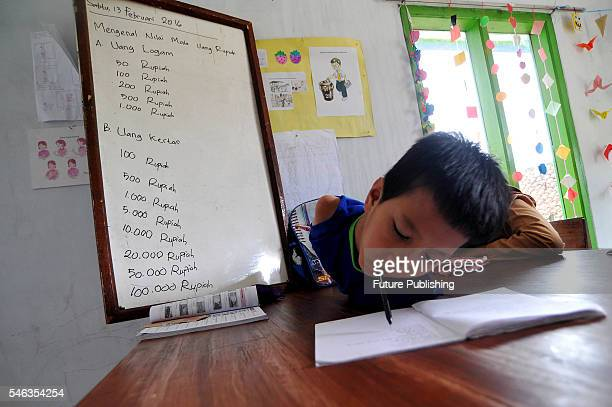 Tyo Satrio a little boy born without arms and legs writing at school in Panawangan Ciamis on February 13 2016 in West Java Indonesia BORN without...
