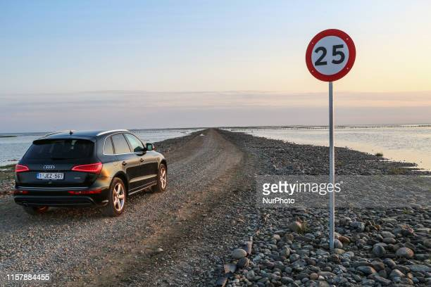 Type Audi Q5 car on the gravel road by the The Wadden Sea bottom connecting Jutland and Mano Island, opened only few hours daily during low tide due...