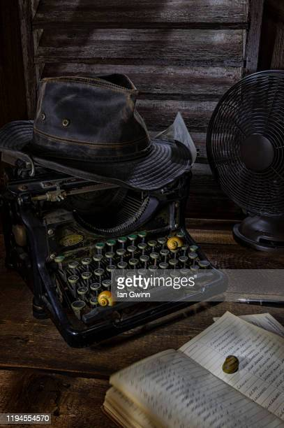 typewriter and indiana jones hat - ian gwinn stock pictures, royalty-free photos & images