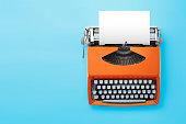 Typewriter machine in retro style on blue background.