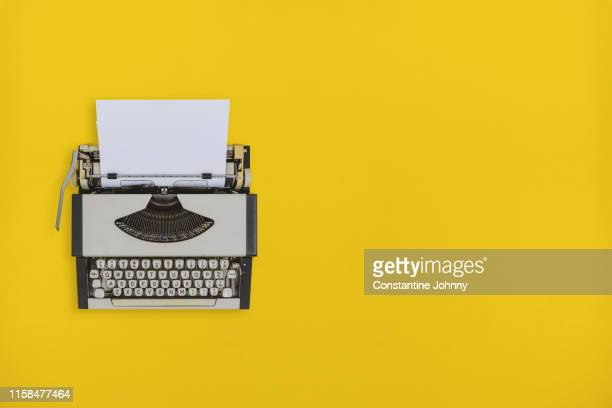 typewriter on yellow background - storytelling stock pictures, royalty-free photos & images