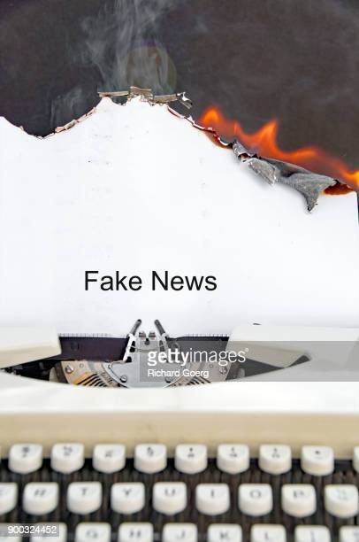 typewriter with burning paper - fake news fotografías e imágenes de stock