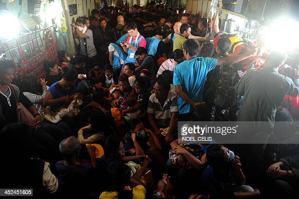 Typhoon survivors ride onboard a C-130 military plane out of Tacloban, Leyte province, to Manila on November 29, 2013. The Philippines' economy...