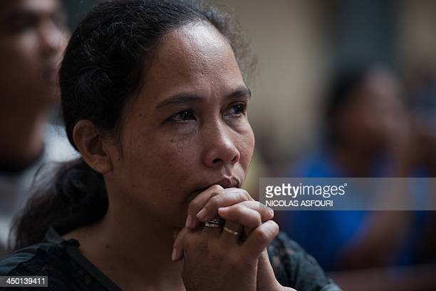 A typhoon victim prays during a mass at the Santo Nino church in Tacloban on November 17 2013 The United Nations has confirmed at least 4500 killed...