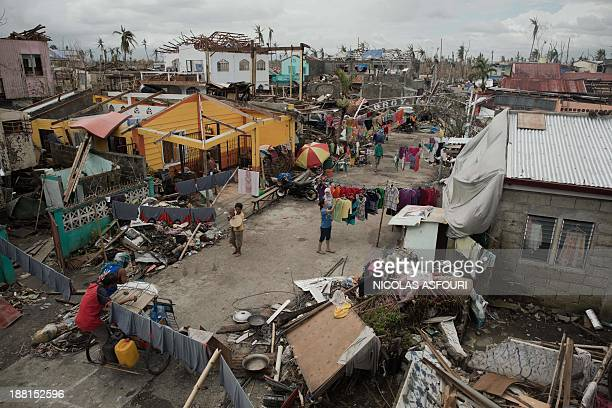 Typhoon victim walks past debris on a street in Tanauan, on the outskirts of Tacloban on November 16, 2013. Spearheaded by a US aircraft carrier...