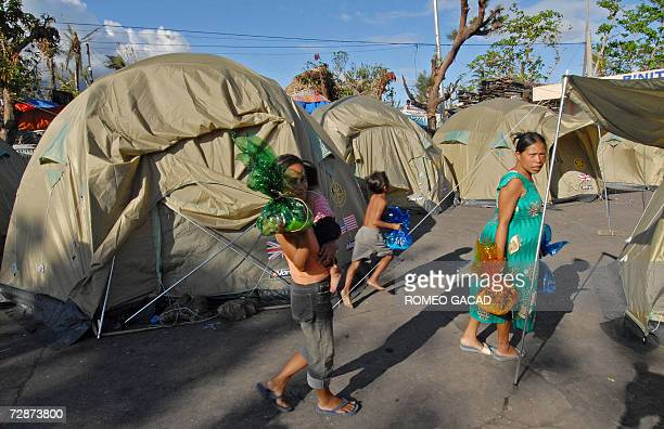 Typhoon victims carry donated toys at an typhoon evacuation center at the Binitayan elementary school where thousands displaced families will spend...