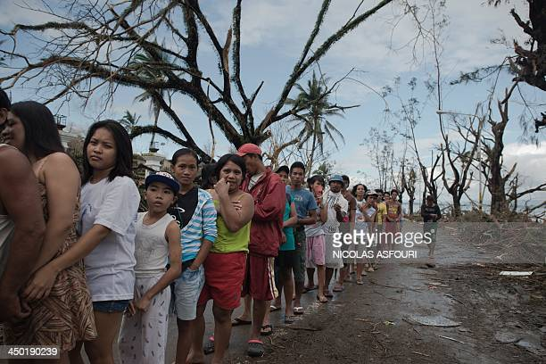 Typhoon victims queue to get relief food at the legislative building in Tacloban on November 17 2013 Grieving survivors of a monster typhoon in the...
