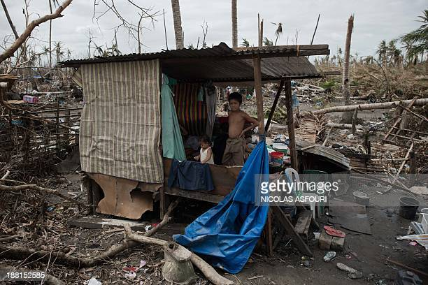 Typhoon victims stand in a temporary shelter after their house was destroyed during Super Typhoon Haiyan in Tanauan, on the outskirts of Tacloban on...