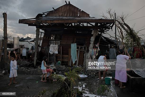 Typhoon victims stand outside their destroyed house in the aftermath of typhoon Haiyan in Jaro on the eastern Philippine island of Leyte on November...