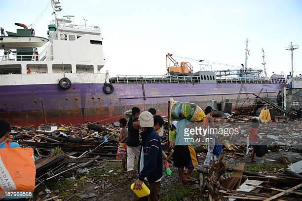 Typhoon-affected residents walk past a ship swept ashore at the height of Typhoon Haiyan in Tacloban city, Leyte province, central Philippines on...