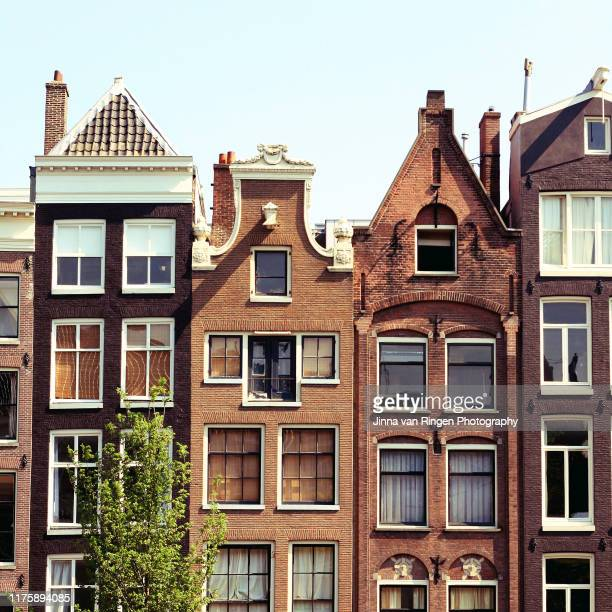typical amsterdam canal row houses - amsterdam stock pictures, royalty-free photos & images