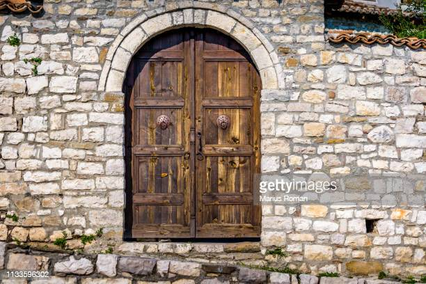 typical arched wooden door in the old fortified city of berat, albania, unesco world heritage site. - castle stock-fotos und bilder