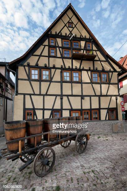 typical building facade with a cart full of wine barrels,eguisheim. - emreturanphoto stock pictures, royalty-free photos & images