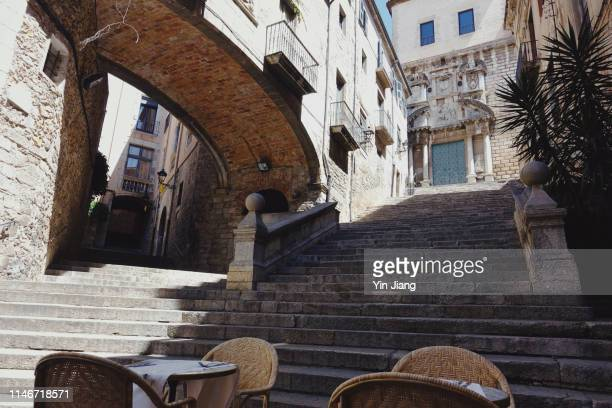 typical corner of the old quarter of girona (pujada de sant domènec) and steps of sant marti sacosta church - gerona city stock pictures, royalty-free photos & images
