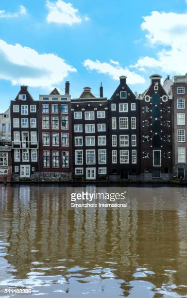 Typical Dutch architecture with a row of old houses reflected on canal waters, Amsterdam, Netherlands