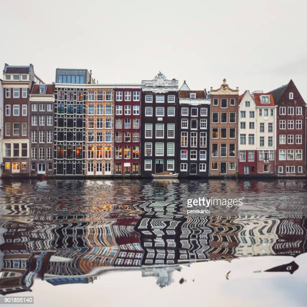 typical dutch houses built by the canal, amsterdam, netherlands - dutch culture stock photos and pictures