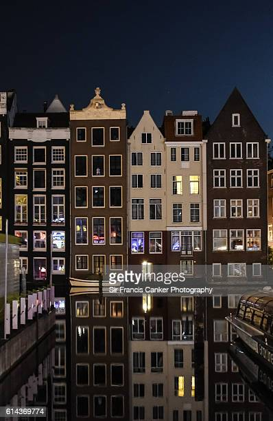 Typical Dutch houses built by the canal and reflected on water at night in Amsterdam