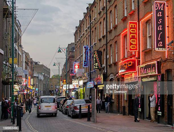 Typical early evening scene of Bangladeshi curry restaurants with their neon signs in Brick Lane, East London. The doormen are ready to entice the...