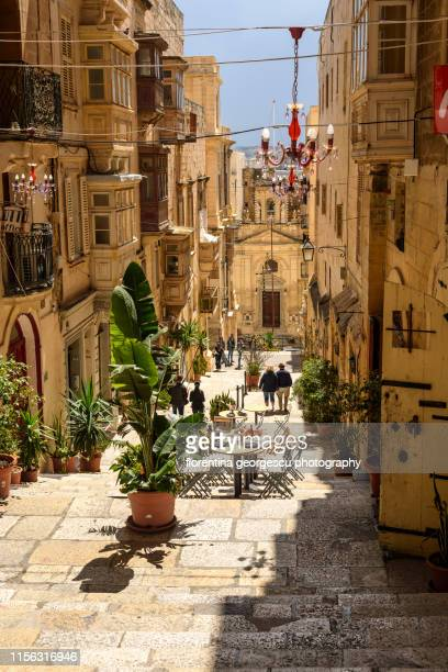 typical enclosed maltese balconies flanking a narrow cobbled alley with steps to the grand harbor, valletta, malta - valletta stock pictures, royalty-free photos & images