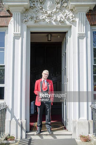 typical english man standing in door with key - red pants stock photos and pictures
