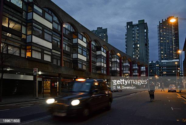 Typical evening scene in Clerkenwell, London. The Barbican Towers are in the backdrop. A London taxi drives past. A cyclist is on his bike. The...