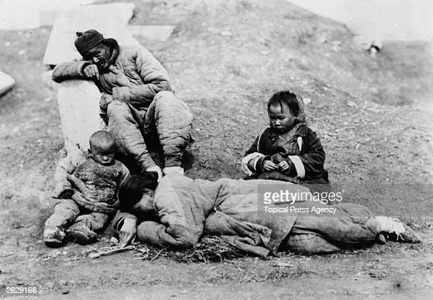 Typical famine victims in China. A man grieves while children look at dying mother.