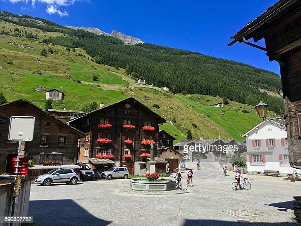 Typical Graubünden market square and green meadows in background.