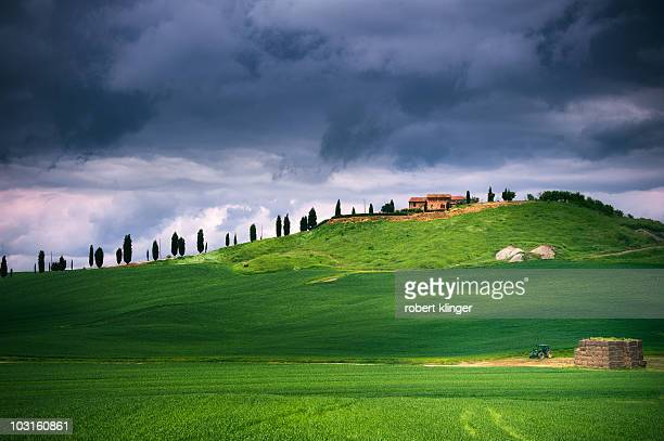 Typical green hill in tuscany with a stormy sky in the background