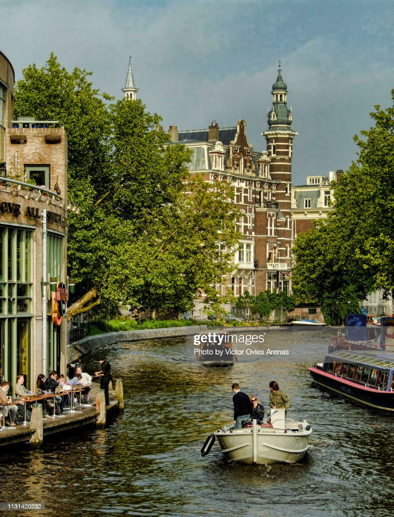 Typical image of a canal in Amsterdam in summer with boats bar terraces : Foto de stock