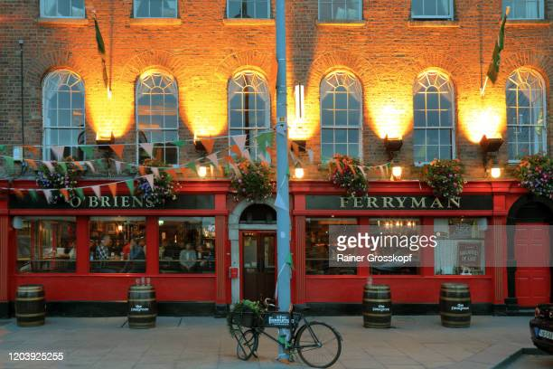 typical irish pub illuminated at dusk - rainer grosskopf stock pictures, royalty-free photos & images