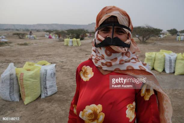 A typical native woman wearing a burka on her face seen during packing of dried fish laid on the ground on May 1 2017 in Qeshm Island Iran The dried...