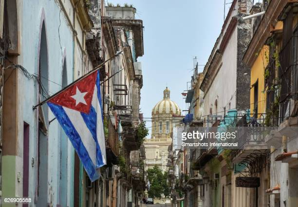 typical old havana street with cuban flag and museo de la revolucion dome on background - cuban flag stock pictures, royalty-free photos & images