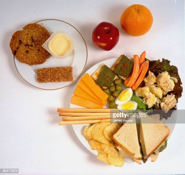 Typical Olympic athlete's lunch of sandwich breadsticks olives crackers potato salad chips egg cheese carrots apple orange granola bar pudding big...