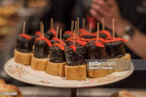 typical pintxos, tapas, of black pudding, morcilla, served in san sebastian, donostia, basque region, spain. - san sebastian spain stock pictures, royalty-free photos & images