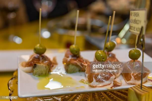 typical pintxos, tapas, of iberico ham white tuna served in san sebastian, donostia, basque region, spain. - san sebastian spain stock pictures, royalty-free photos & images