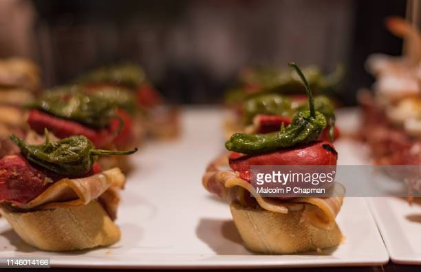 typical pintxos, tapas, of padron pepper and ham served in a san sebastian, basque region, spain. - san sebastian spain stock pictures, royalty-free photos & images