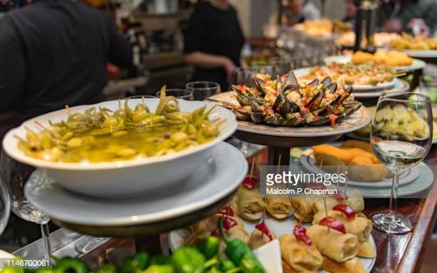 typical pintxos, tapas, on a bar counter in san sebastian, donostia, basque region, spain. - san sebastian spain stock pictures, royalty-free photos & images
