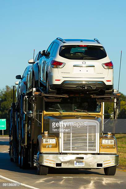 Typical shiny American Freightliner truck transporting new automobiles car transporter on route Interstate 10 Louisiana USA