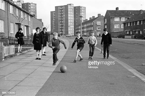 Typical street in Kirkby, Liverpool. Boys playing football in the street, they are members of the St. John's Ambulance Brigade and their cry was...