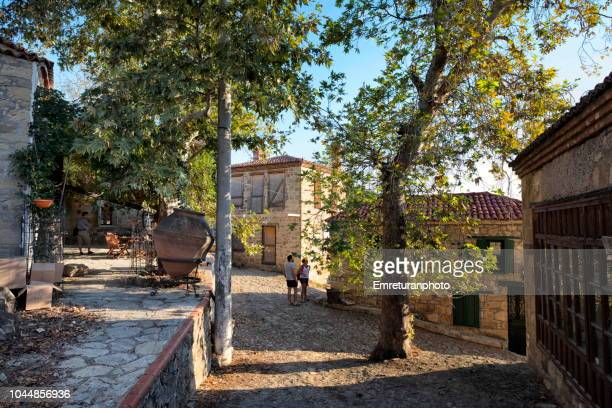 a typical street of adatepe village with some tourists. - emreturanphoto stock pictures, royalty-free photos & images