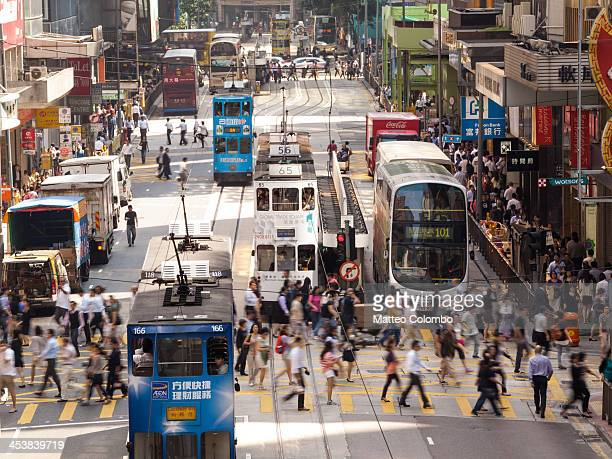 Typical street scene in Hong Kong, with traditional trams and buses, and a crowd of people crossing the road. Elevated view, at day time. Admiralty...
