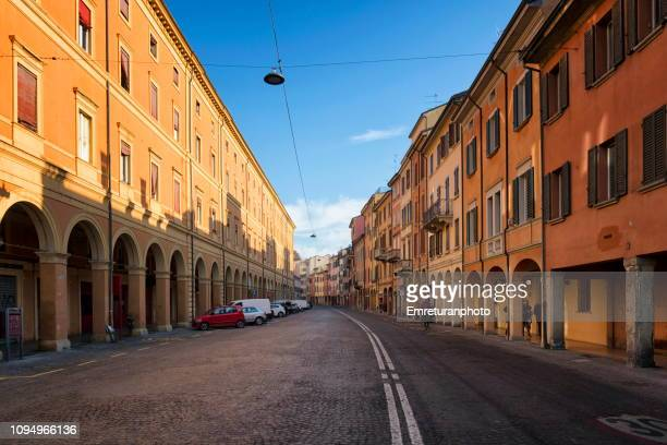 a typical street with porticos on both sides in bologna - emreturanphoto stock-fotos und bilder