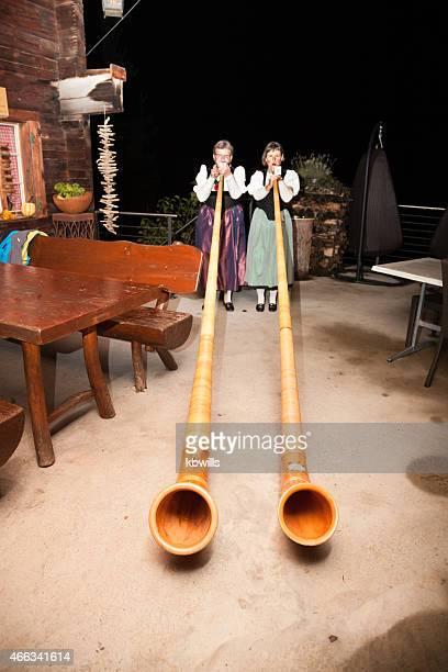 Typische Schweizer Damen spielen Alphorn Café im Freien