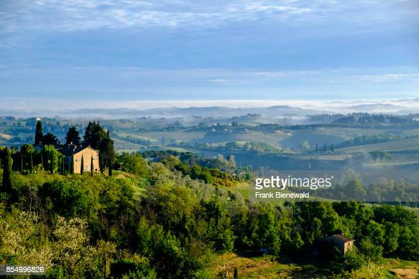 Typical tuscanian landscape with a farmhouse on a hill, vineyards and morning fog.