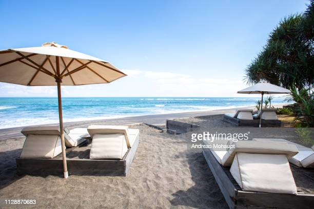 typical umbrellas on the beach in canggu, bali island, indonesia - andreas solar stock pictures, royalty-free photos & images