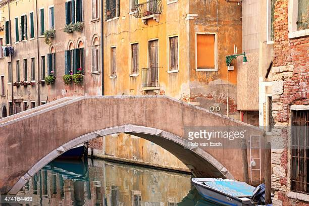 CONTENT] Typical view on old quaint houses in Venice along a canal and a bridge visible part of the image Boat is floating The image has a warm look...