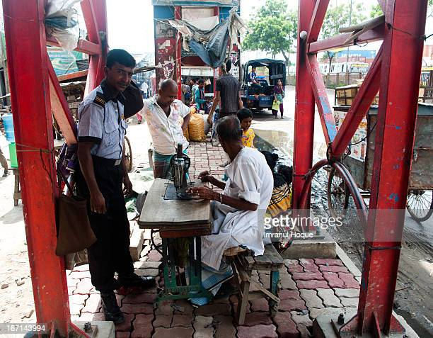 Typical view under the foot over bridges of dhaka. Tea stalls, hawkers and this old man is here with his sewing machine. This is Dhaka, the city of...