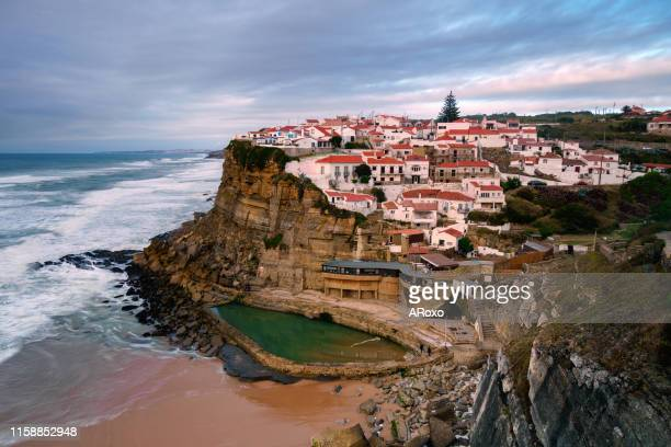 typical village on the seaside cliff at sunset. amazing seascape near lisbon. coastal landscape and tourist attraction of portugal. sintra natural park. - cascais stock photos and pictures